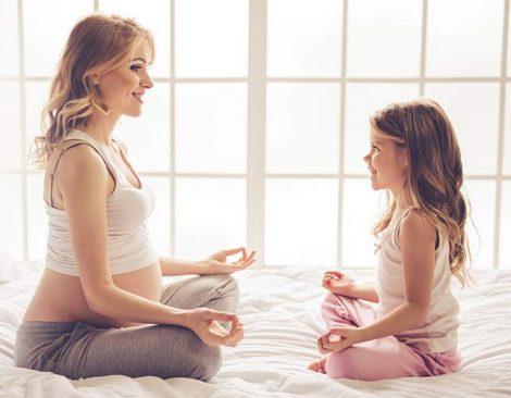 Madre embarazada haciendo ejercicios de yoga con su hija